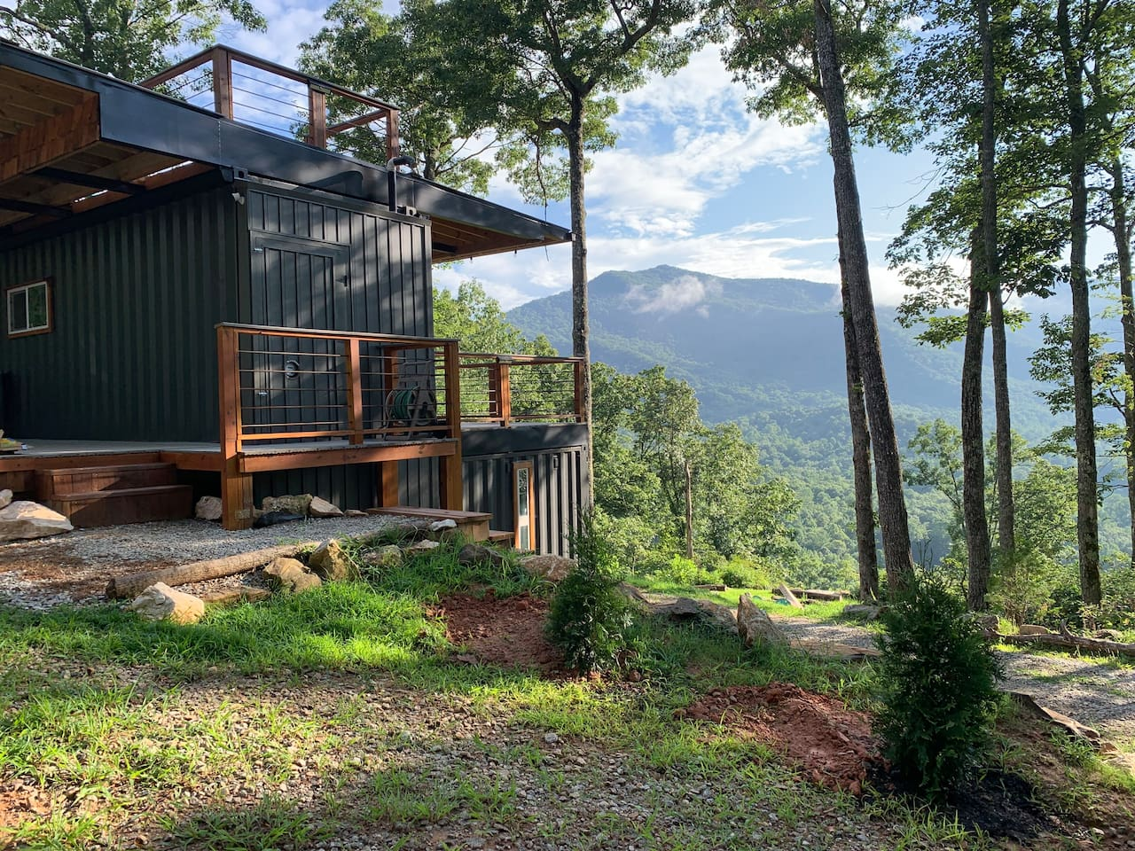 After you pass our gate and navigate the long winding driveway you will approach a modern tiny home built out of shipping containers, tucked high in the Smokey Mountains.
