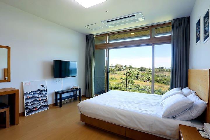 침실모습입니다. 퀸사이즈의 호텔식침구가 놓여있고 통유리를 통해 멋진 뷰를 볼 수 있어요.