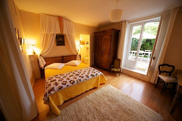 Bedroom, with bathroom in the back and access to patio on the right