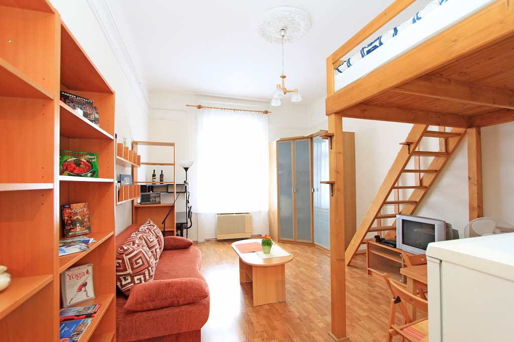 Light flooded bright living room with sleeping gallery upstairs and automatic window shutters from the bed