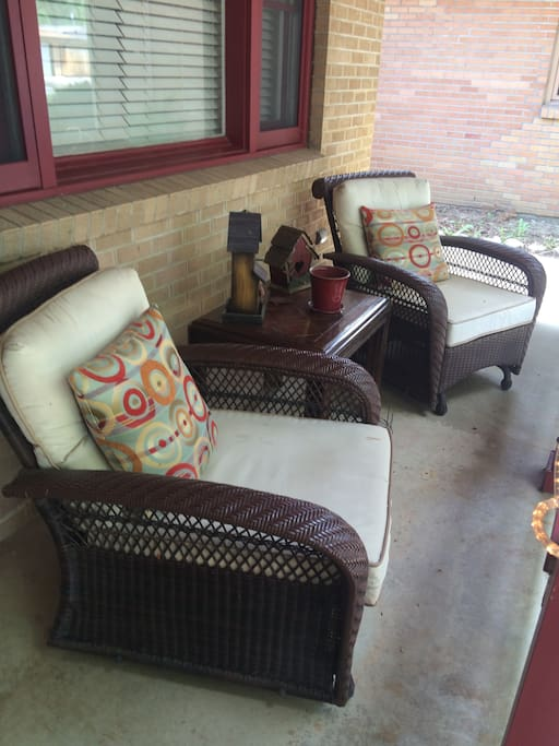 Front porch with glider chairs. Lovely maples and pine tree shade the sun.