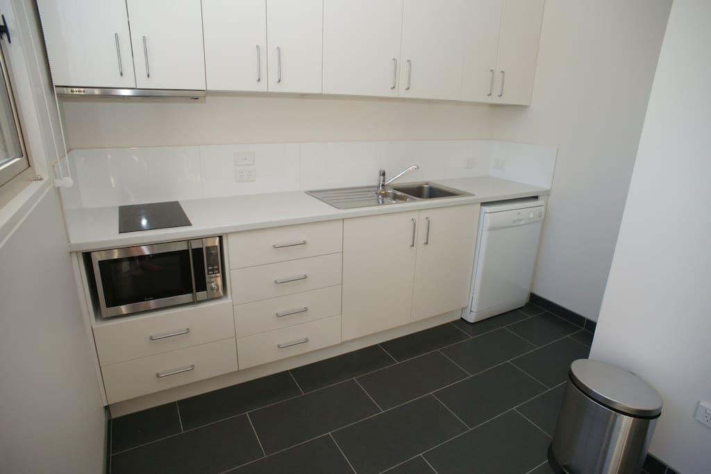 Kitchen area. Full sized fridge opposite the dishwasher.