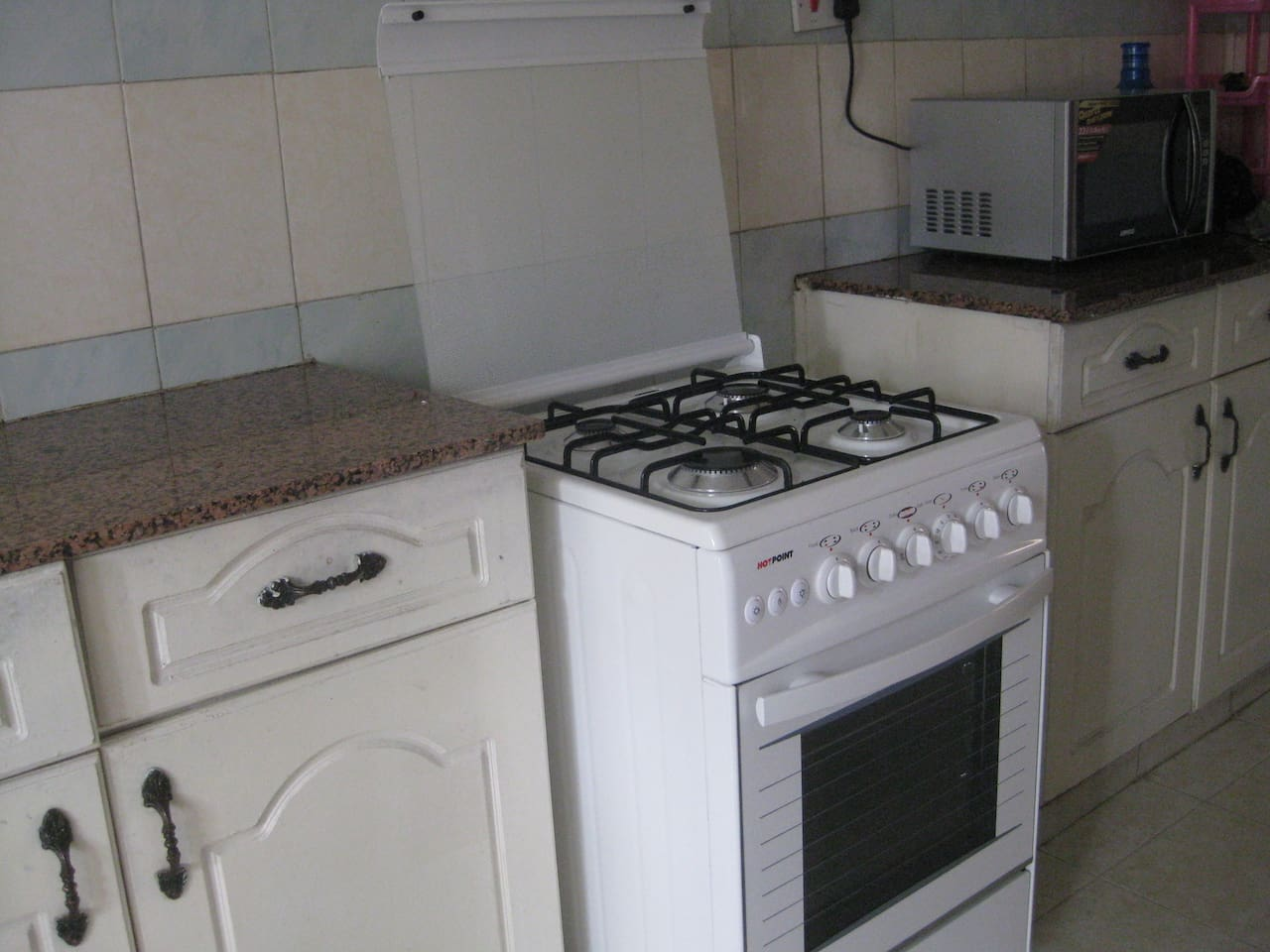 fitted kitchen with a gas cooker, microwave, electric kettle and a toaster