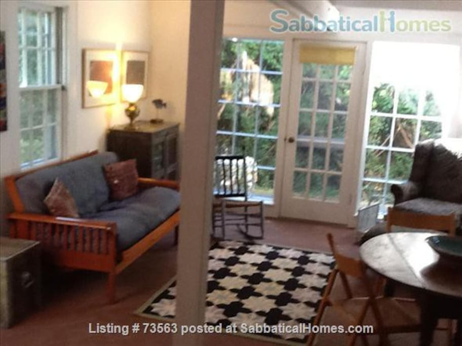 Living/dining area with a futon for two. A private patio is through livingroom door