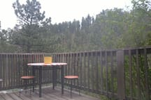 Deck hangs out over edge of hill. Creek below and mountain vistas of National Forest lands adjacent to property makes for peace and relaxation.