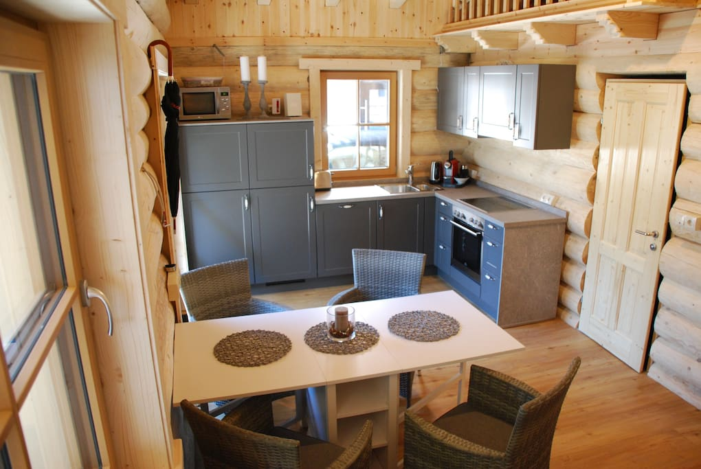 The kitchen is fully equipped with a 4-flame cooker, an oven, a microwave, dishwasher, fridge/freezer.