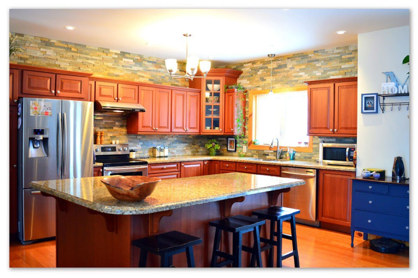 Open concept kitchen with stainless appliances, stone back splash accent walls, and granite counters