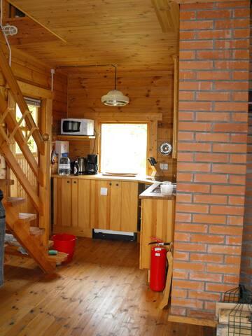 Der Küchenbereich vom Essbereich aus gesehen mit Hauseingang und Treppe zu den Schlafräumen
