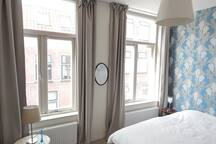 The street-facing front bedroom has a double bed, a single sofa-bed, and the evening light.
