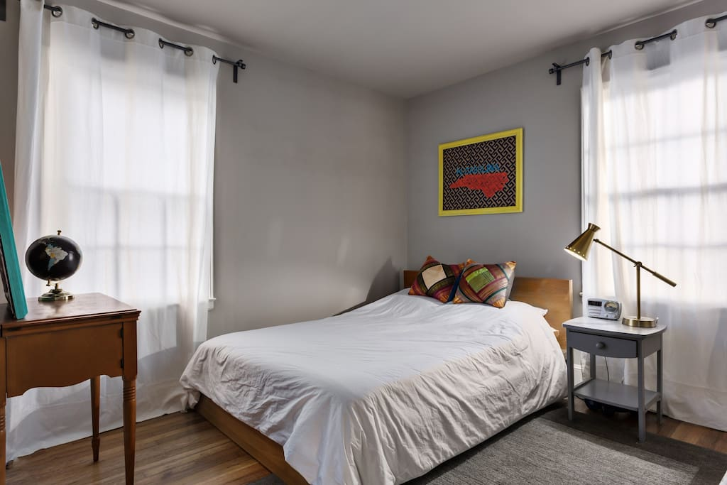 The bedroom is quiet and spacious with a queen bed.