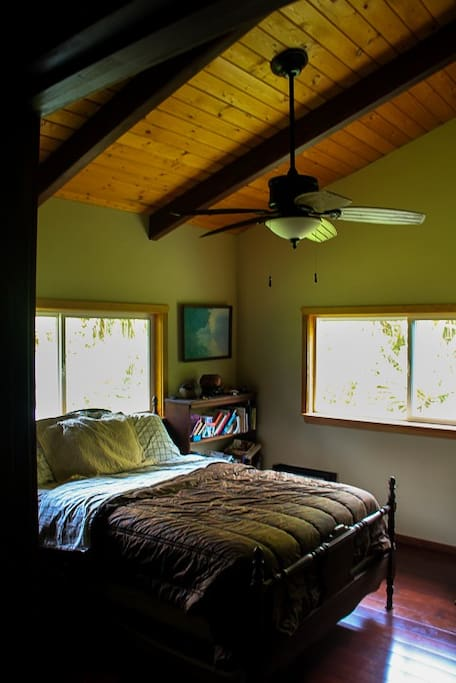 guest bedroom with beautiful vaulted ceilings and wooden floors over looking gardens