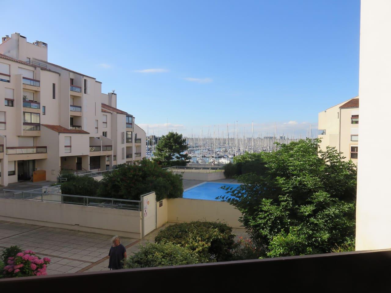 Vue du balcon sur la piscine et le port de plaisance
