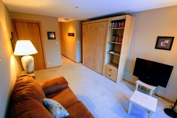 The downstairs living space that converts to the second bedroom.  Folding table and chairs with a fridge, microwave, couch and cable TV make this a great game room: puzzles, board games, cards and poker chips provided.