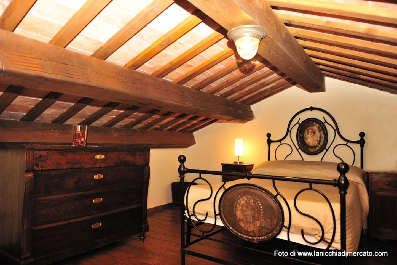 Il letto sul soppalco, con arredi d'epoca, come tutto l'appartamento