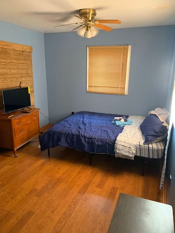 Large bedroom with closet,smart TV, and dresser