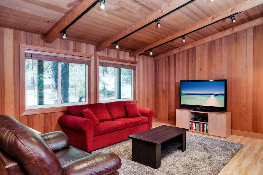 """The living area provides a plush sofa (which folds out into a queen-sized bed), a leather armchair, and a 55"""" TV."""