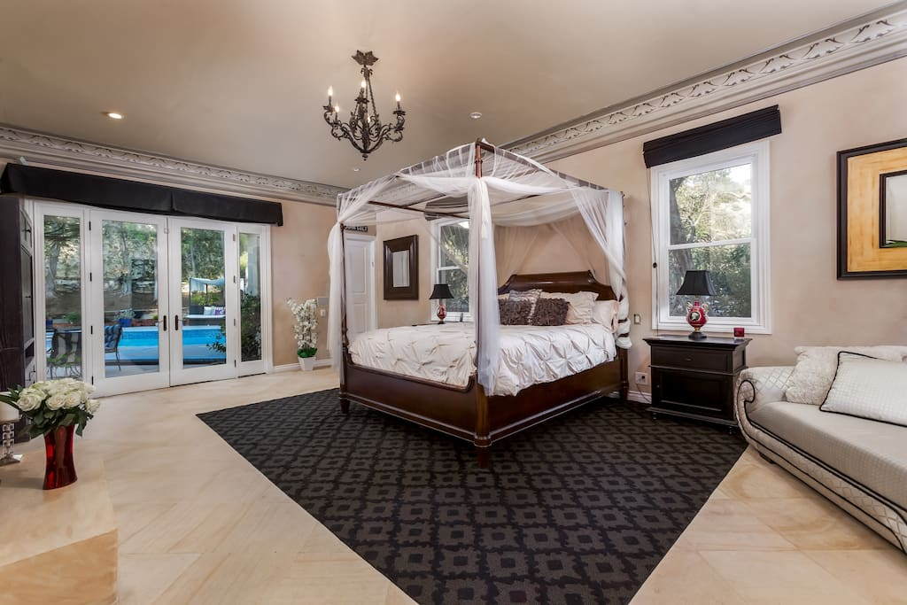 The master suite also features a chaise lounge sitting area as well as seating by the pool directly outside of the French doors.