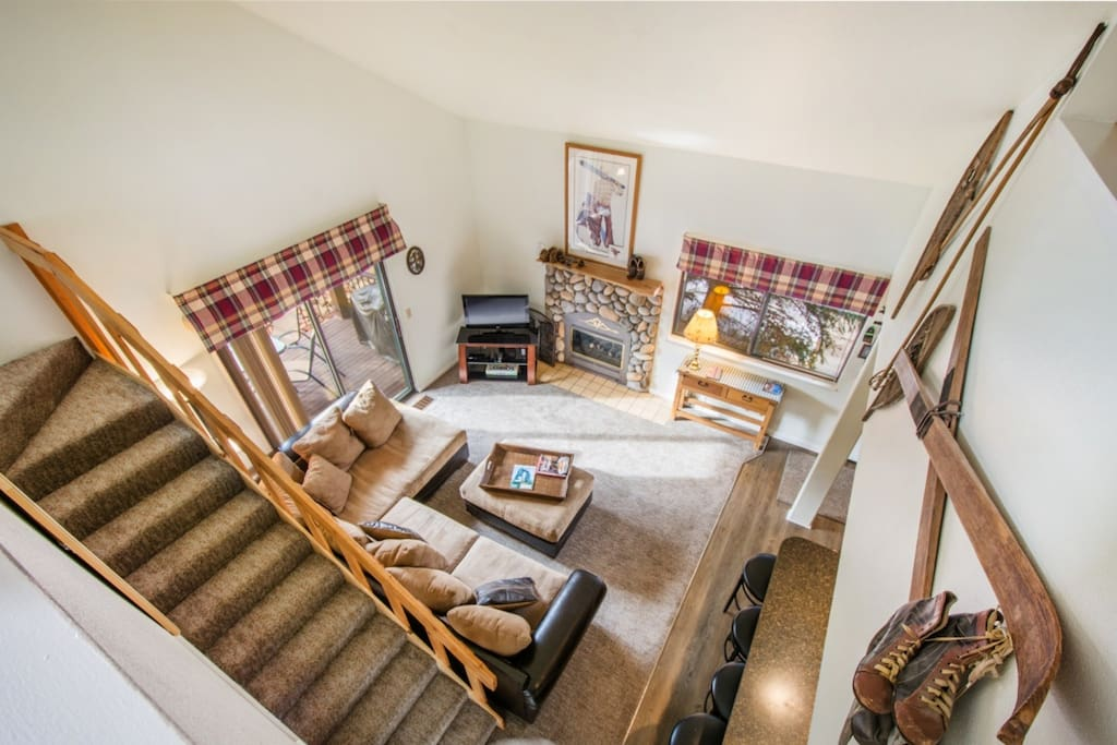 Living room is well equipped with plush and comfortable furniture, stone fireplace, HDTV with satellite and antique ski decor.