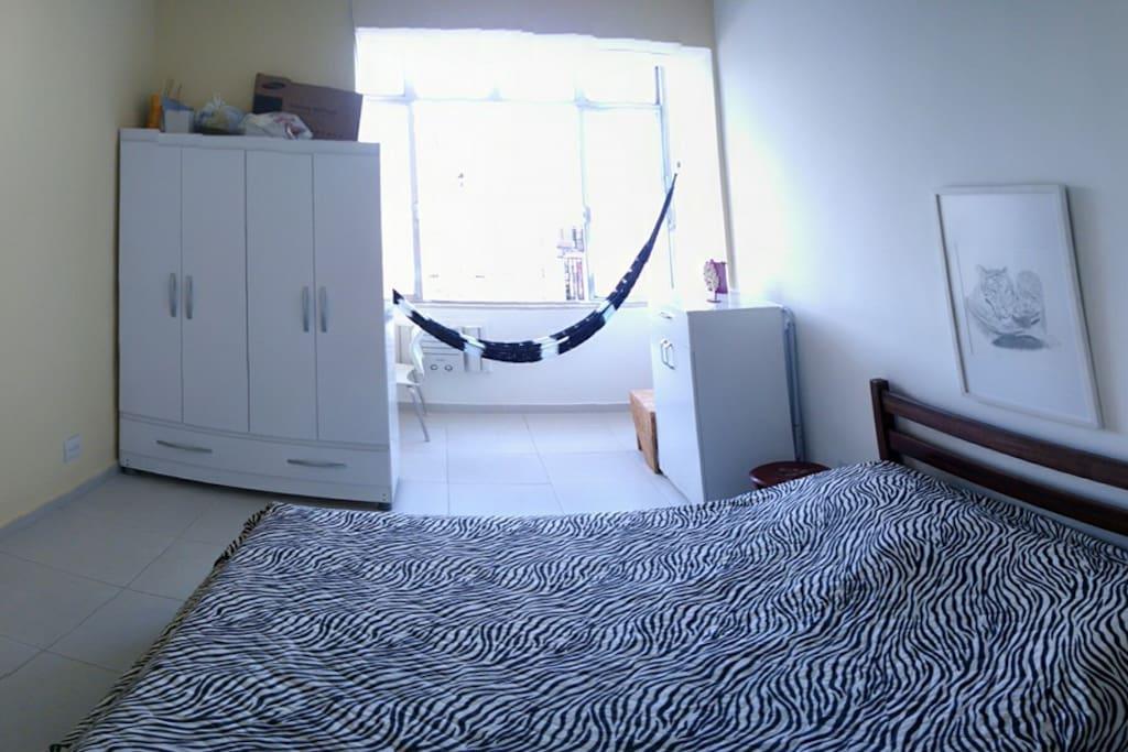 Quarto com janelão (muito claro! A luz está apagada), cama de casal, ar condicionado, ventilador de teto, armário 4 portas, mesa de cabeceira, mesinha de estudos com cadeira, rede e cômoda
