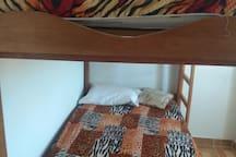Habitación con camarote , además cuenta con cama de dos plazas,  closet y mesa de noche