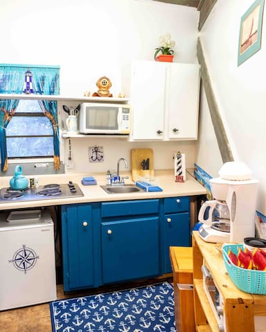 Kitchen with 4 burner stove, toaster oven, small fridge. All pots, pans & dishware included.