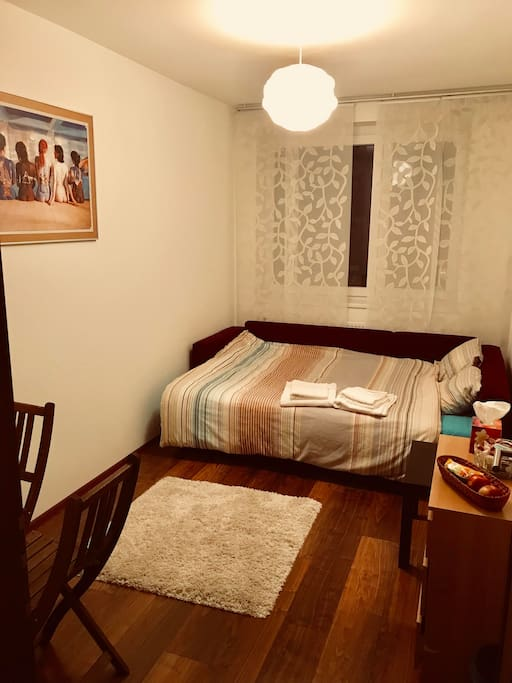 Clean and cozy bedroom with double bed, 3 drawer unit, table with 2 chairs and a closet. Also a complementary basket of chocolate and candies :)