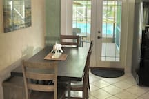 The kitchen table and the double doors to the patio and pool.
