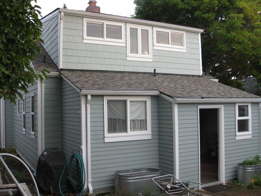 Back of house leads out to small patio. Second-story office/bedroom with western views of Olympic Mountains.