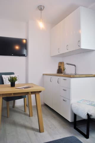 The kitchen is fully equipped with dishes, fridge and glass ceramic plate.