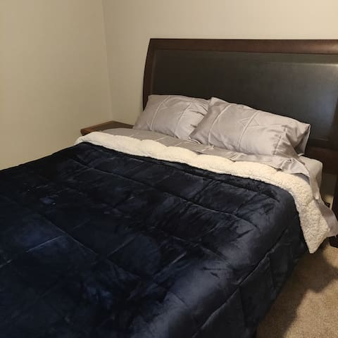 Queen bed, with additional pillows and set of blankets