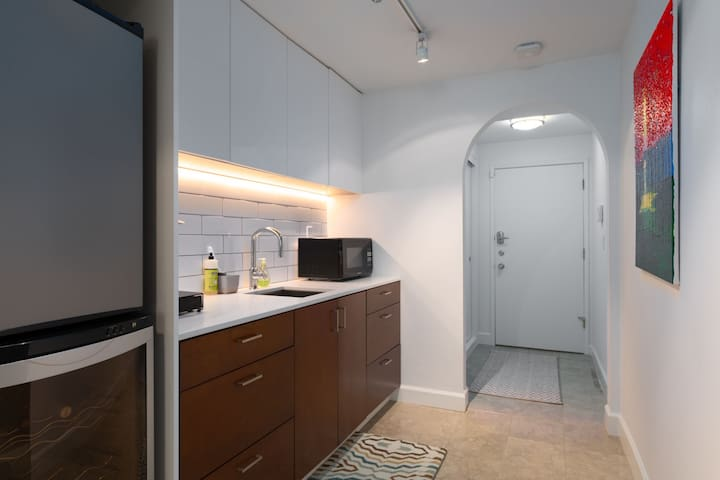 Kitchenette area with refrigerator, sink, cabinets, and appliances (microwave, Keurig coffee maker, tea kettle, etc.)