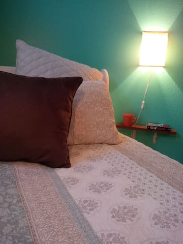 Both sides of the bed have a lamp and shelf for your phone and coffee