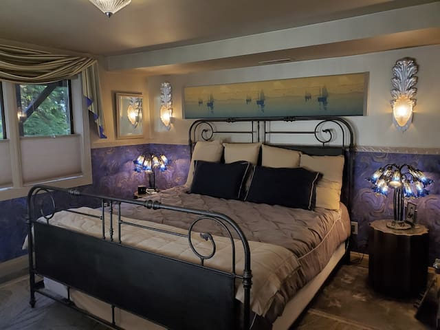 The master bedroom offers a unique violet-gold theme with custom Deco sconces designed by your host.