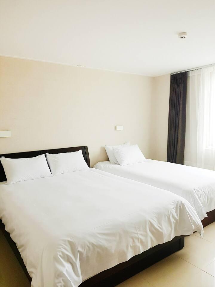 침대 2개가 준비되어 있는 깔끔한 화이트톤 인테리어의 201호(DELUXE TWIN)