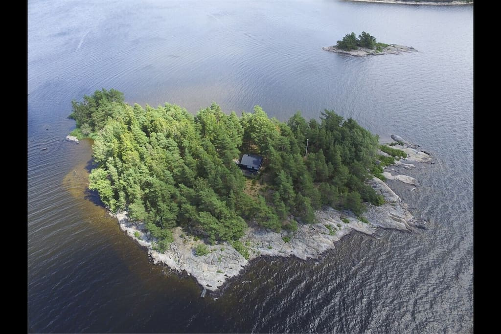 Main house embedded in the forest as seen from a western bird eye perspective visualizing the south shore great for recreational activities with it's large and lavishly smooth rocky surfaces great for swimming and sunbathing whilst with ease maintaining visual contact with children >4 years can play supervised along >1/3 of the islands total shoreline.