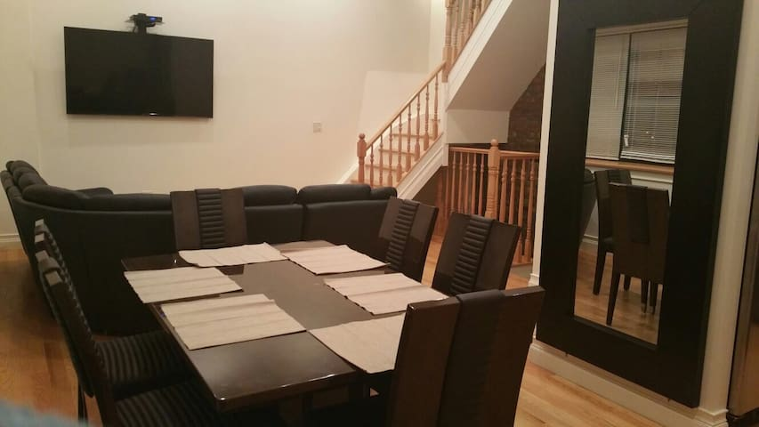 First floor. Dinning table with seating for 8. Also living room area with flat screen TV.