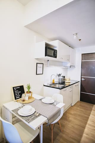 The kitchenette is fully equipped with a 2 burner induction cooker with range hood, refrigerator, rice cooker, electric kettle, dinnerware, cookware, microwave oven, basic condiments, cleaning tools, and closet cabinet for storage.