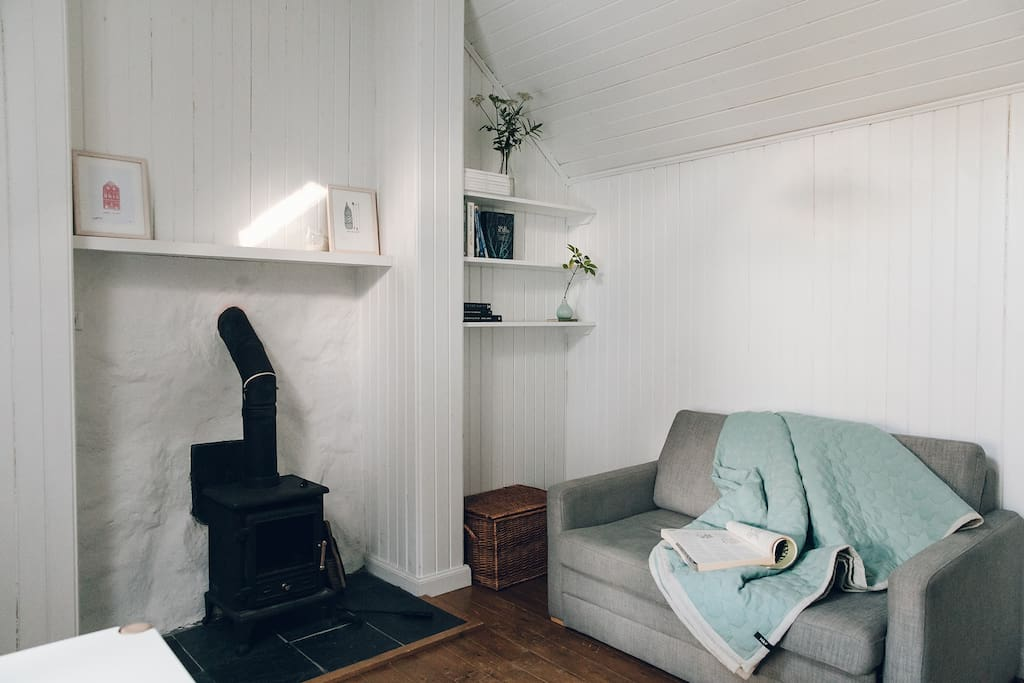 """Living room with wood/peat burning stove, sofa, flat screen 32"""" tv, dvds, books, board game, bluetooth portable speaker"""
