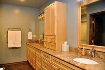 Large bath with dual vanities, walk-in shower, heated towel rack, granite countertops, and plenty of storage.