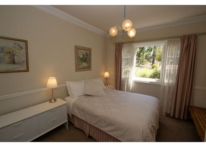 The main bedroom is a restful retreat with garden views.