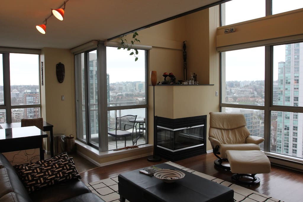 Another view of the living room; there's a small balcony with two chairs, a table, and a gas grill.