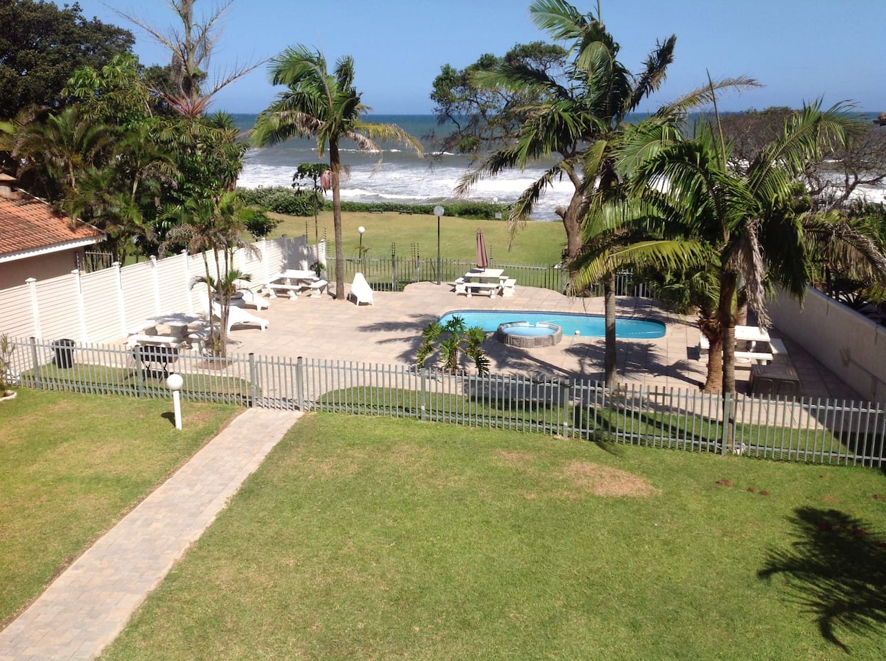 An aerial view of the pool area and deck with gate leading to the beach.