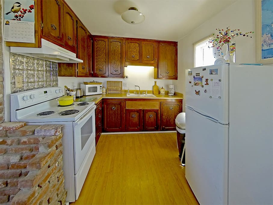 The kitchen is fully appointed with appliances, microwave, pots, pans, stoneware and silverware.