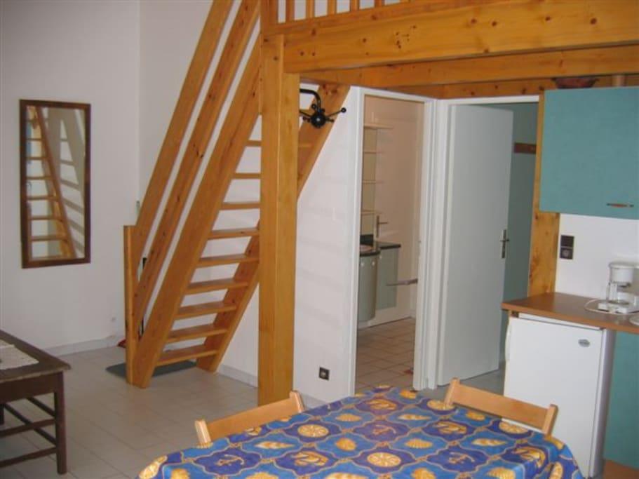 séjour, escalier vers mezzanine, portes salle de bains et chambre