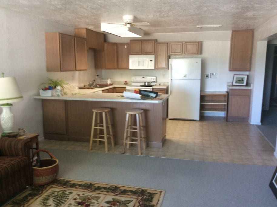 "Fully equipped kitchen with range, oven, toaster, microwave, coffee-maker, and ""thing-charger"" on island."