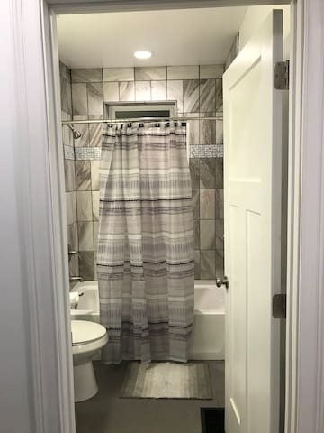 View of the full bath on the first floor! All luxurious towels and linens provided, just for you! You'll find the hairdryer you need and extra essentials in the drawers. Each bedroom also has an assortment of amenities in case you forget anything! No worries here!
