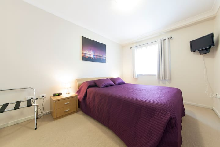 Queen size bedroom including wall mounted TV