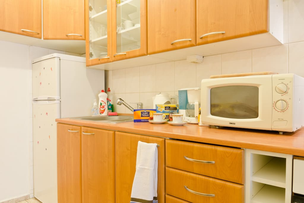 Kitchen supplied with handsoap, dish towels, sponges, cutlery, dishes, and cookware