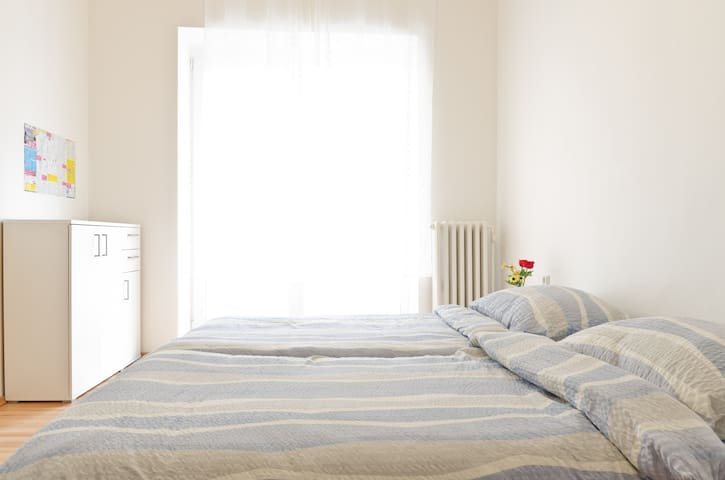 Also available in blue: this room contains 3 single beds (two here and one on the loft), a balcony (that's where the light is coming from),  a table and chairs and two night tables.