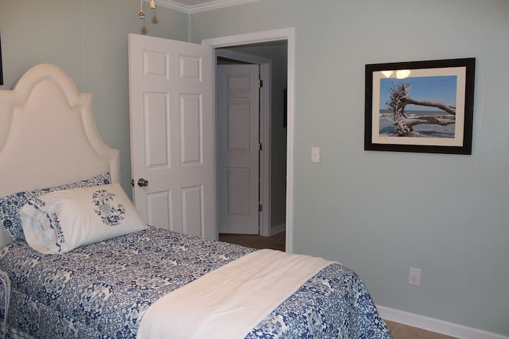 Twin Bedroom with Ralph Lauren comforters.  LR and kitchen separate the master and twin bedrooms.